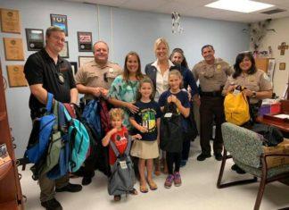 Ocaquatics Swim School joins village to distribute backpacks